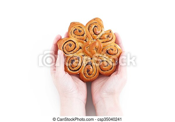 female hand holding a loaf of bread with poppy seeds - csp35040241