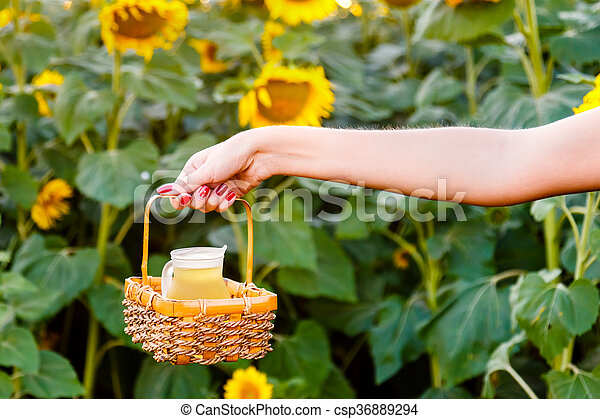 Female hand holding a wicker basket with a jug of sunflower oil  - csp36889294