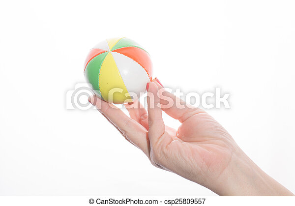female hand holding colored juggling balls on a white background - csp25809557