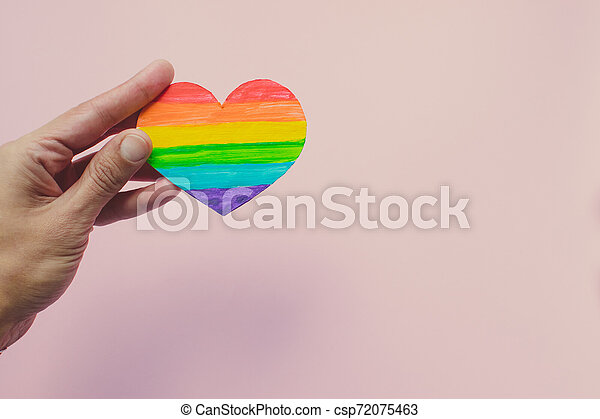 Female hand holding decorative Heart with rainbow stripes on pink background. LGBT pride flag, symbol of lesbian, gay, bisexual, transgender. Homosexual love, Human rights concept. Copy space. - csp72075463