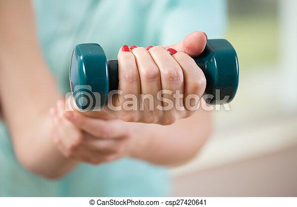 Female hand holding dumbbell - csp27420641