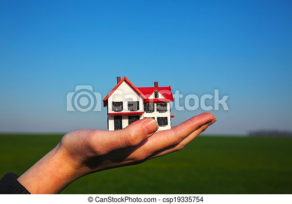 Female hand holding model of residential building - csp19335754