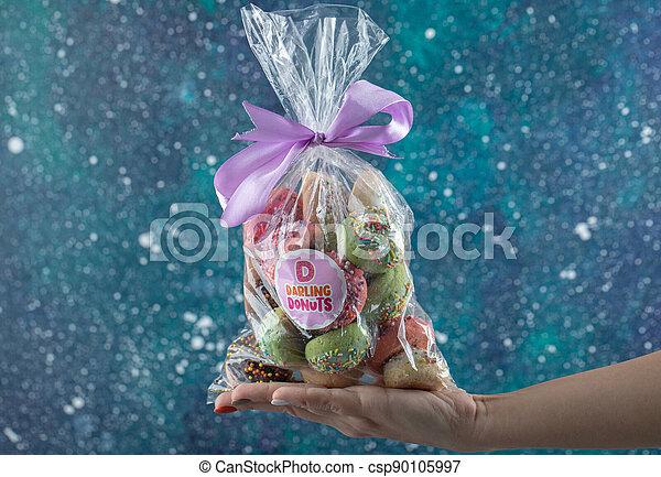 Female hand holding plastic bag of cookies - csp90105997
