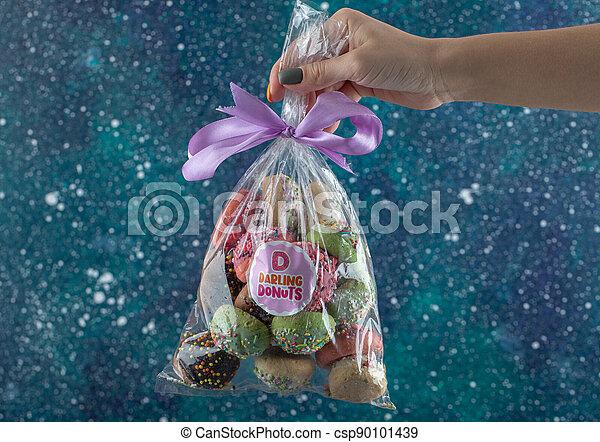Female hand holding plastic bag of cookies - csp90101439