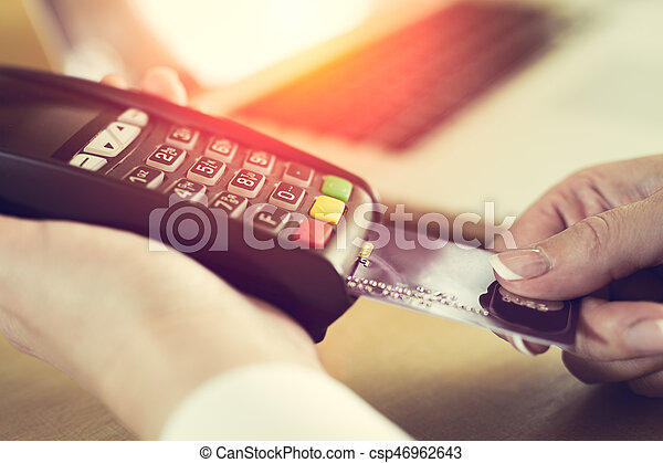 Female hand inserting credit card into a reader - csp46962643