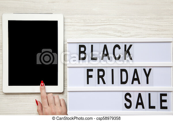 Female hand using tablet, 'Black friday sale' word on lightbox over white wooden background, top view. From above, overhead. - csp58979358