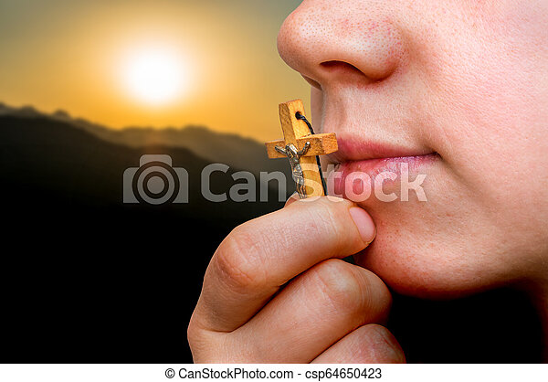 Female hand with wooden cross and sunset in the mountains - csp64650423