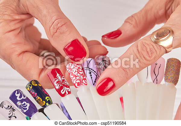 Female Hands Choosing Nail Design Old Woman Hands With Red Manicure