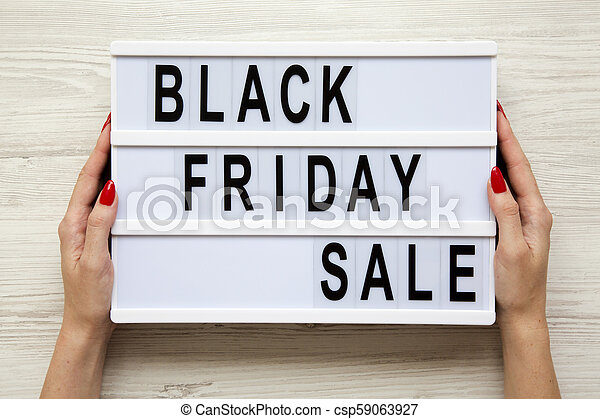 Female hands hold 'Black friday sale' word on lightbox over white wooden background, top view. From above, overhead. - csp59063927