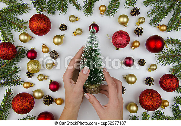 Female hands holding a decorative christmas tree. Christmas composition made of gold and red balls for a Christmas tree, and fir branches. Winter flat lay. - csp52377187