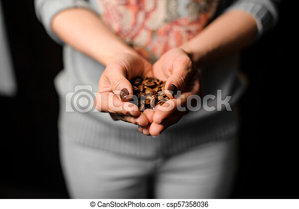 Female hands holding a handful of fresh coffee beans - csp57358036