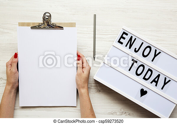 Female hands holding an empty noticepad over white wooden background, top view. 'Enjoy today' word on lightbox. From above, flat-lay, overhead. - csp59273520