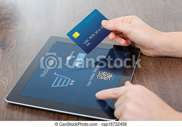 female hands holding credit card and a computer tablet on the table in the office and making a purchase onlain  - csp18722456