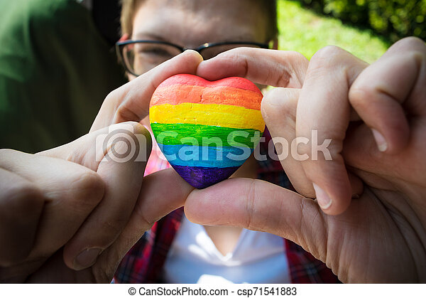 Female hands holding decorative Heart with rainbow stripes. LGBT pride flag, symbol of lesbian, gay, bisexual, transgender for social movements. Homosexual love, Human rights concept. Copy space. - csp71541883