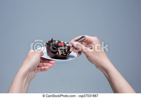 Female hands keeping cake with spoon on gray - csp37031887