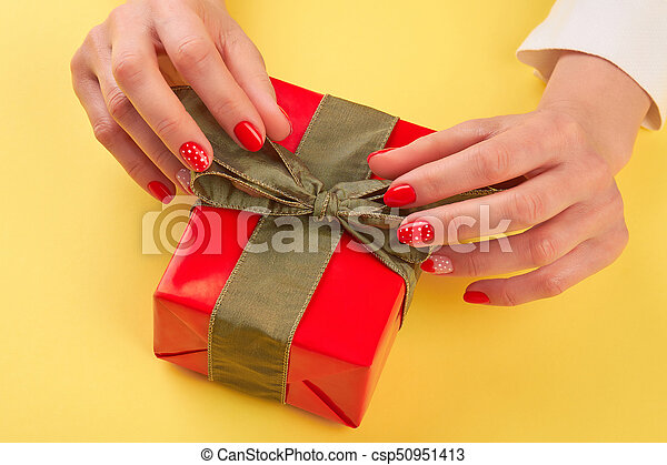 Female hands unpacking red gift box. Young woman manicured hands opening red box with present isolated on yellow background. Holiday present concept.