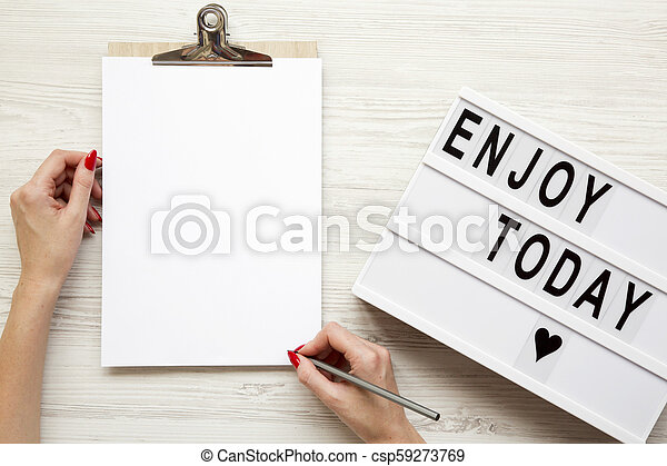 Female hands with an empty noticepad and 'Enjoy today' word on lightbox over white wooden background, top view. From above, flat lay, overhead. - csp59273769