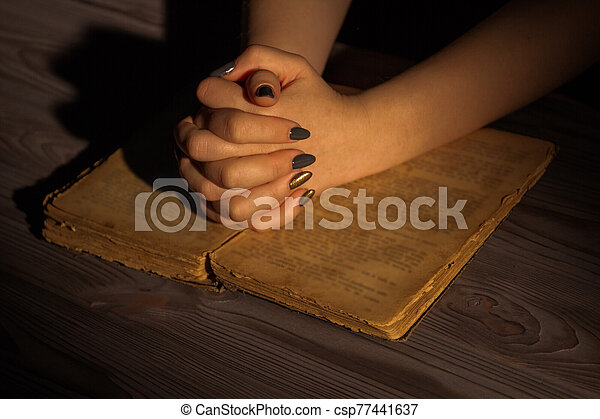 Female hands with folded hands on holy bible. - csp77441637