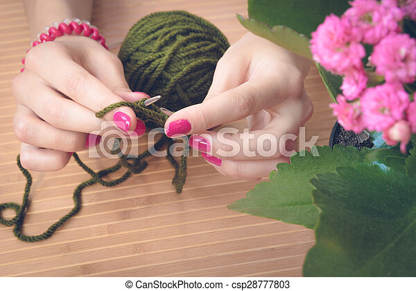 Female hands with purple manicure are knitted metal spokes of a wooden table - csp28777803