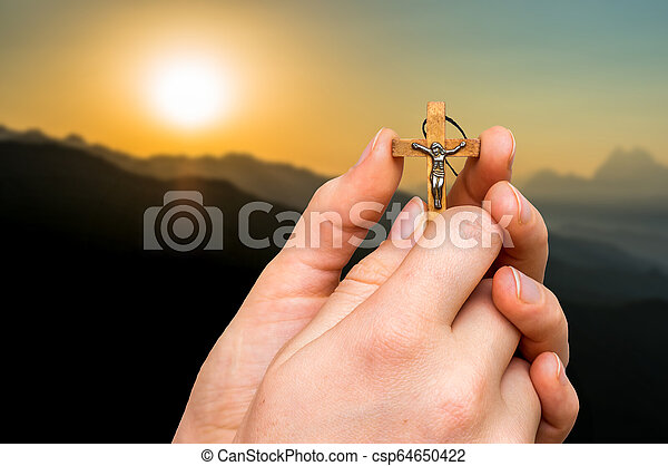 Female hands with wooden cross and sunset in the mountains - csp64650422