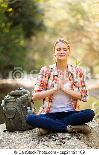 young female hiker yoga meditation in mountain