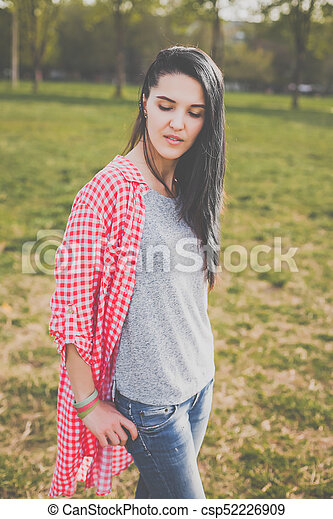 3330314b96a8f6 female hipster in red shirt and ripped jeans posing in park - csp52226909