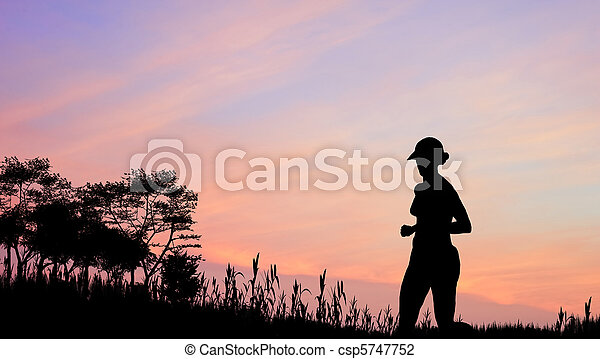 Female jogger silhouette against stunning colorful sunset sky - csp5747752