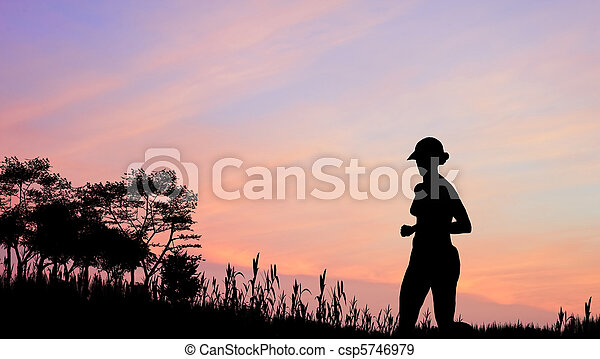 Female jogger silhouette against stunning colorful sunset sky - csp5746979