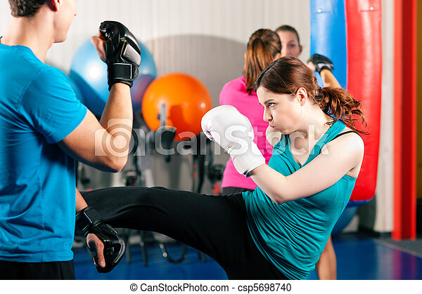 Female kick boxer with trainer in sparring - csp5698740