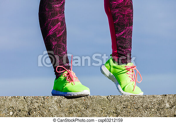 Female legs feet in vivid color yellow shoes on seaside. - csp63212159