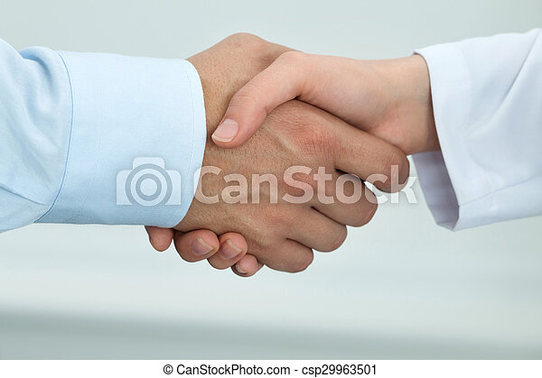 Female medicine doctor shaking hands with male patient - csp29963501