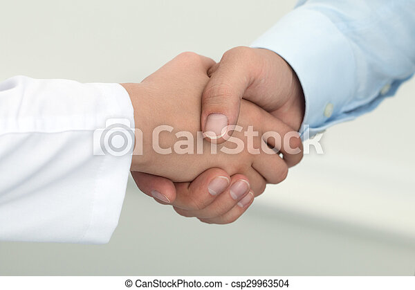 Female medicine doctor shaking hands with male patient. - csp29963504
