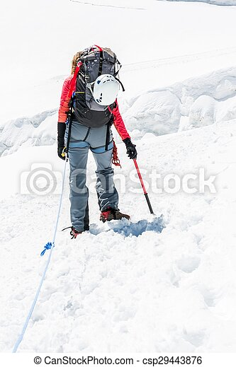 Female mountaineer ascending a glacier. - csp29443876