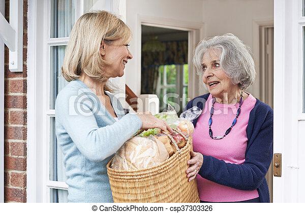 Female Neighbor Helping Senior Woman With Shopping - csp37303326