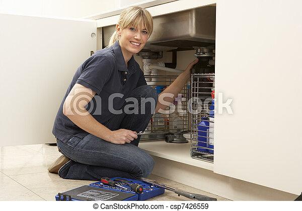 Female Plumber Working On Sink In Kitchen - csp7426559