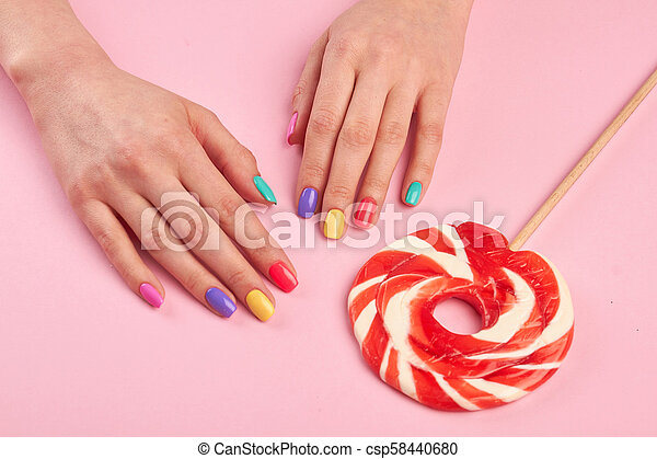 Female polished nails and lollipop