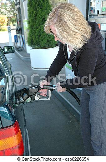 Female pumping gas. - csp6226654
