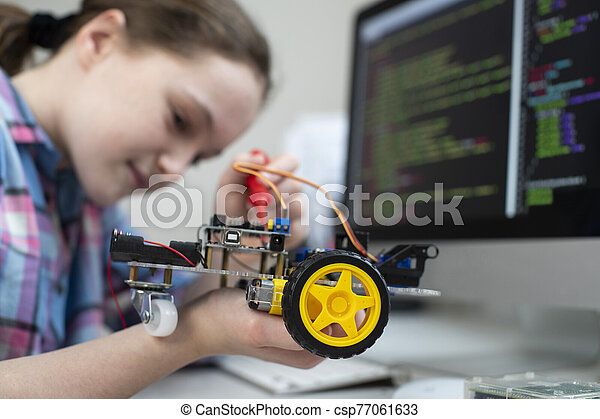 Female Pupil Building Robot Car In School Science Lesson - csp77061633