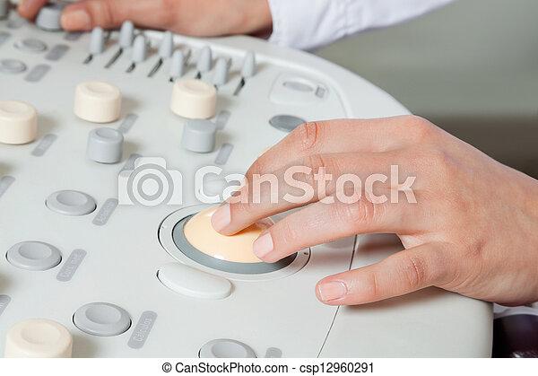 Female Radiologist Operating Ultrasound Machine - csp12960291