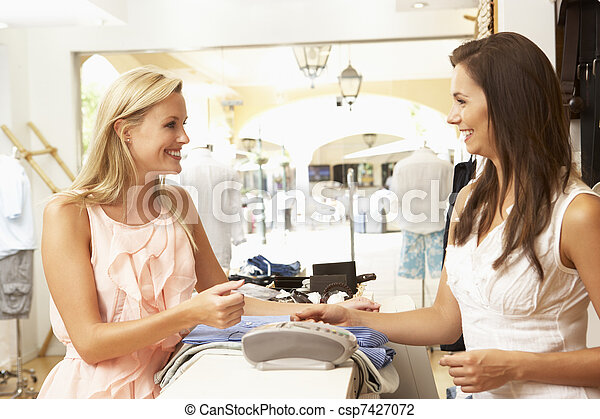 Female Sales Assistant At Checkout Of Clothing Store With Customer - csp7427072