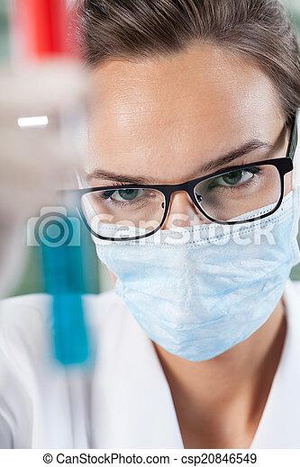 Female scientist examining test tube with blue liquid - csp20846549