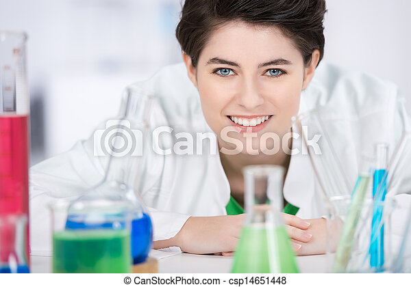 Female Scientist With Chemicals On Foreground In Laboratory - csp14651448