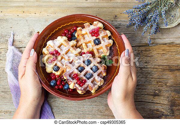 Female serving homemade waffles fresh berry fruit - csp49305365