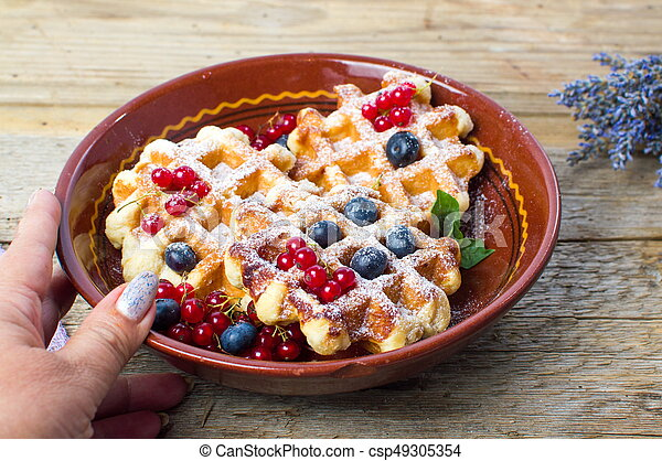 Female serving homemade waffles fresh berry fruit - csp49305354