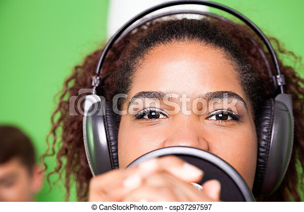 Female Singer Wearing Headphones While Performing - csp37297597