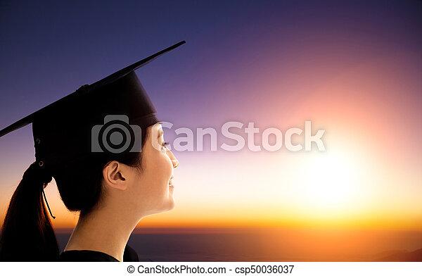 female Student Celebrating Graduation watching the sunrise - csp50036037