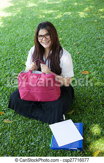 Female student sitting on the lawn. - csp27716077