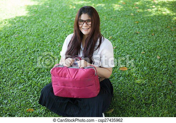 Female student sitting on the lawn. - csp27435962