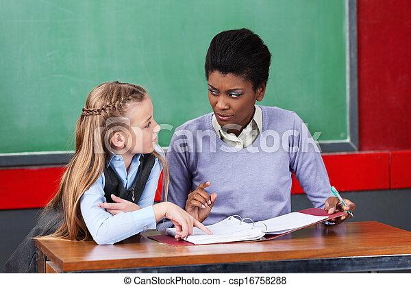Female Teacher Looking At Schoolgirl In Classroom Csp16758288