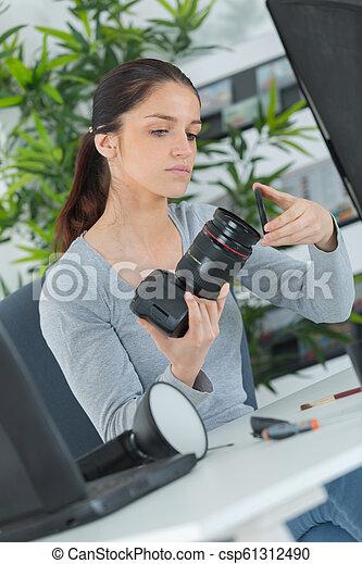 female technician doing the maintenance of a camera - csp61312490